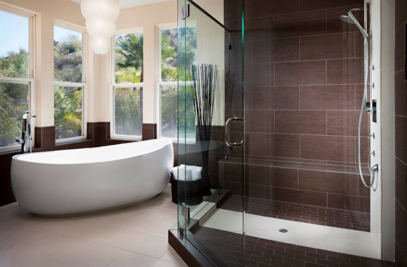 Wainscoting that mimics the shower tile works as a backdrop for this freestanding soaking tub.